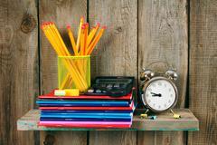 Writing-books, an alarm clock and school tools . - stock photo