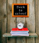 Back to school. An alarm clock and writing-books Kuvituskuvat