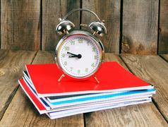 Alarm clock and writing-books . Stock Photos