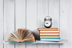 Open book, multi-coloured books and alarm clock. - stock photo