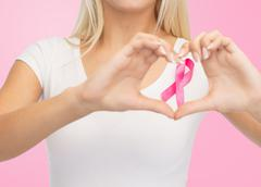 close up of woman and pink cancer awareness ribbon - stock photo