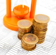 Sand-glass and gold a coin. On documents - stock photo