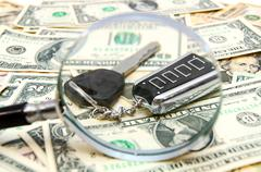 Magnifier and key from the car on banknotes Stock Photos