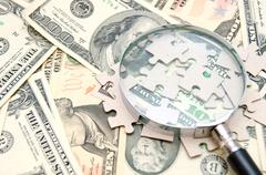 Magnifier and puzzle on money - stock photo