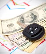 Dollars and key from the car on graphs - stock photo