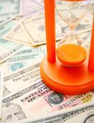Sand-glass on dollars - stock photo