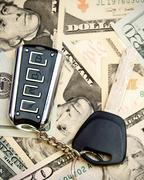 Key from the car on dollars - stock photo