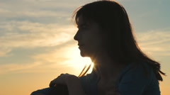 Silhouette Profile of Woman Sitting Against Sunset HD - stock footage