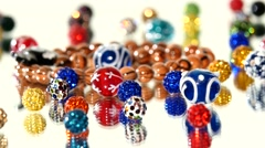Lot of varicolored beads on white background, rotation, reflection Stock Footage