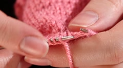 Woman sits and knits pink scarf, fine knit, close up, slow motion Stock Footage