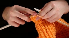Woman sits and knits orange scarf, large knit, on black background, slow motion Stock Footage