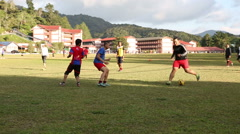 Young guys playing soccer in Tanah Rata, Cameron Highlands, Malaysia Stock Footage