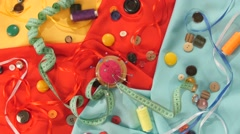 Tailor spools of colorful thread, buttons, pincushion, measuring tape on yellow - stock footage