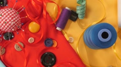 Colorful thread, buttons, pincushion, measuring tape on yellow, red and blue Stock Footage
