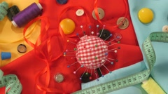 Top of colorful thread, measuring tape, buttons, pincushion on yellow, red and - stock footage