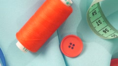 Threads, measuring tape and buttons on blue cloth, close up Stock Footage