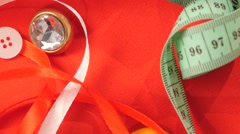 Ribbons, threads, measuring tape and buttons on red cloth, close up Stock Footage
