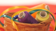 Basket with colorful threads, needles and ribbons, close up Stock Footage