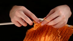 Woman sits and knits orange scarf, large knit on black background, close up Stock Footage