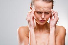Beautiful woman suffering from acute headache over grey clean ba Stock Photos