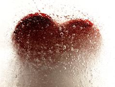 Red heart embedded in ice. - stock photo