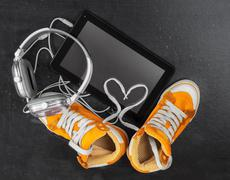 Orange sneakers, headphones, tablet . - stock photo