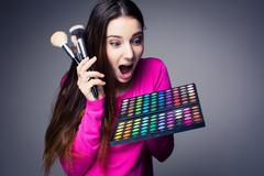 Cute make-up artist holding her vast palette of colors and hands Stock Photos