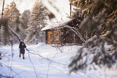 Caucasian woman walking near log cabin in snowy forest Stock Photos