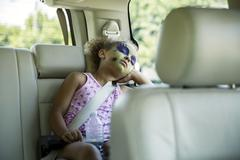 Mixed race girl in face paint sleeping in car back seat Stock Photos