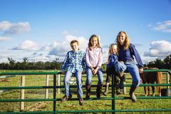 Caucasian farmer and children sitting on fence on ranch Stock Photos