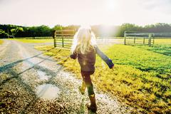Caucasian girl walking on dirt road on ranch Stock Photos