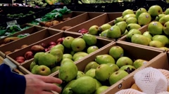 Man selecting pear in grocery store - stock footage