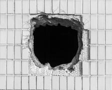 Hole on the old white wall - stock photo