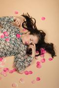 atractive brunette girl lying on beige background - stock photo