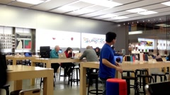 Motion of customers and shop assistants at the Apple store. - stock footage