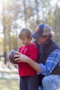 Caucasian father teaching son to play football Kuvituskuvat
