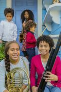 Pacific Islander family holding musical instruments on front stoop Stock Photos