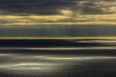 Sunbeams shining over ocean seascape Stock Photos