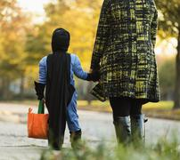 African American boy trick-or-treating with mother on Halloween Stock Photos