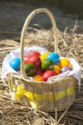 Colourful Easter eggs inside straw wicker Stock Photos