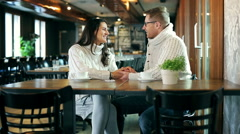 Couple holding hands and chatting in the restaurant Stock Footage