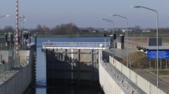 LOCK EMPEL, THE NETHERLANDS - Steel gate opens, rhine barge approache Stock Footage