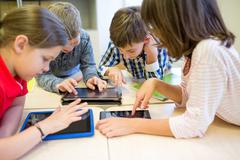 group of school kids with tablet pc in classroom - stock photo