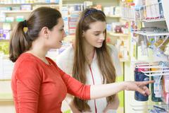 Young female pharmacist having a customer in a drugstore - stock photo