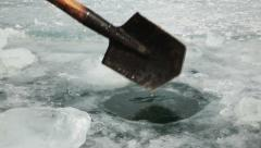 Hole in the ice  Man with a shovel chop a hole in the ice Stock Footage