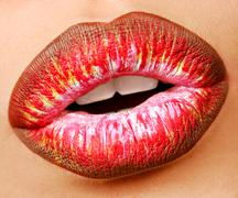 Stock Photo of Multi colored lipstick with temptation gesture. Close-up lips. Macro shot.