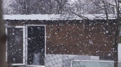 Large snowflakes falling in slow motion with background old shack Stock Footage