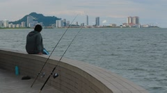 A man fishing While Overlooking the Komtar View Stock Footage