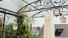 Close-up of a white wedding dress hanging under the roof of the terrace in the s Stock Footage