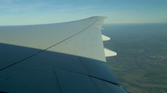 View over landscape & aircraft wing in flight Stock Footage